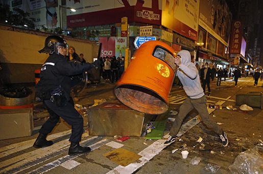A rioter tries to throw a litter bin at police on a street in Mong Kok district of Hong Kong, Tuesday, Feb. 9, 2016. Hong Kong's Lunar New Year celebration descended into chaotic scenes as protesters and police, who fired warning shots into the air, clashed over a street market selling fish balls and other local holiday delicacies, leaving dozens injured and arrested. (AP Photo/Kin Cheung)