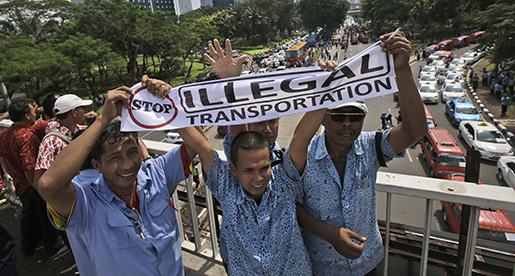 Taxi drivers shout slogans during a protest against competition from ride-hailing apps such as Uber and Grab at the main business district in Jakarta, Indonesia, Tuesday, March 22, 2016. (AP Photo/Achmad Ibrahim)
