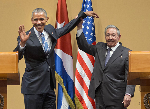 Cuban President Raul Castro lifts up the arm of President Barack Obama at the conclusion of their joint news conference at the Palace of the Revolution, Monday, March 21, 2016 in Havana, Cuba. (AP Photo/Pablo Martinez Monsivais)