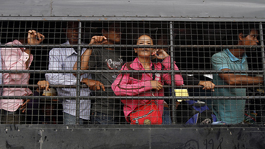 Cambodian migrant workers stand in a truck as they arrive from Thailand at a Cambodia-Thai international border gate in Poipet, Cambodia, Tuesday, June 17, 2014. The number of Cambodians who have returned home from Thailand this month after a threatened crackdown on foreigners working illegally has topped 160,000, a Cambodian official said Monday. Thai officials insist the cross-border movement is voluntary and is not forced repatriation. They say Thai military and government resources were used to transport workers who decided to return home after being laid off because they were working illegally. (AP Photo/Heng Sinith)
