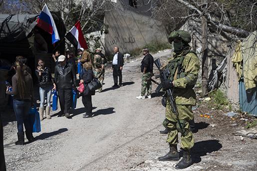 En rysk soldat håller vakt medan humanitär hjälp delas ut i byn Ghunaymiyah, 15 kilometer från Turkiets gräns. Foto: AP Photo/Pavel Golovkin