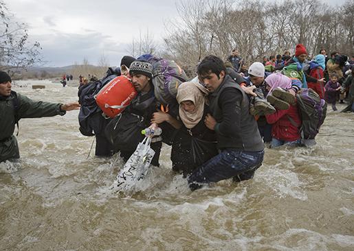Migranter tar sig över gränsfloden. Foto: AP Photo/Vadim Ghirda