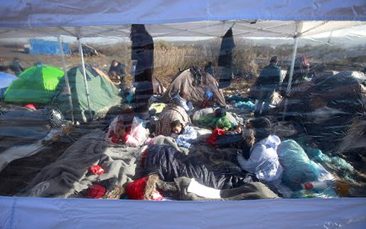 Syriska flyktingar fotograferade genom tältväggen, nära gränsen mellan Makedonien och Serbien. Foto: AP Photo/Boris Grdanoski