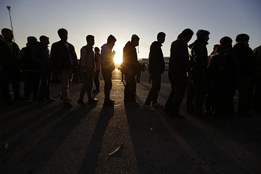 Flyktingar i gryningen i Atens hamn, där de väntar på en matutdelning som en icke-statliga organisation anordnar. Foto: AP Photo/Thanassis Stavrakis