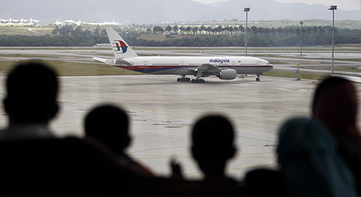 "A Malaysian family is silhouetted against a taxied Malaysia Airlines Boeing 777 plane at the Kuala Lumpur International Airport in Sepang, Malaysia, Saturday, March 5, 2016.   Gibson said Saturday that it would be a ""very lucky discovery"" if the piece of aircraft he found on a sandbank off the coast of Mozambique is confirmed to be from the Malaysia Airlines jet that vanished two years ago. (AP Photo/Joshua Paul)"
