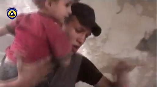 I den här bilden, tagen från en video som publicerades av frivilligorganisationen Syrian Civil Defence den 2 oktober förra året, syns en räddningsarbetare som bär ut ett barn från ett hus som uppges ha bombats av ryska plan i Douma, Syria. Foto: Syria Civil Defence via AP video