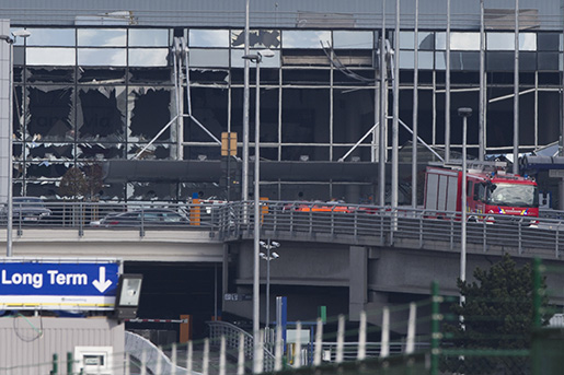 The blown out facade of the terminal is seen as a fire truck drives down the ramp at Zaventem airport, one of the sites of two deadly attacks in Brussels, Belgium, Tuesday, March 22, 2016. Authorities in Europe have tightened security at airports, on subways, at the borders and on city streets after the attacks Tuesday on the Brussels airport and its subway system. (AP Photo/Peter Dejong)
