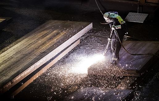 I stålverket har smält stål gjutits till nästan tre decimeter tjocka stora stålstycken som kallas ämnen. Här gashyvlas ämnena innan de valsas till plåt.Foto: Marcus Ericsson