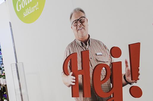 """Herrn på affischen som välkomnar kunderna är butiksägaren Paul Larsson. """"Min förhoppning är att kunna erbjuda mina medarbetare fler timmar"""", säger han till Arbetet. Foto: Karl Melander"""
