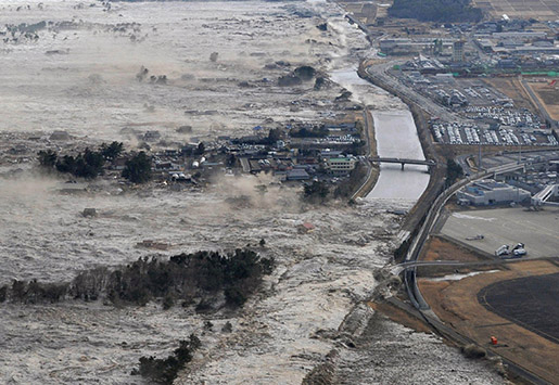 FILE - In this March 11, 2011 file aerial photo, an earthquake-triggered tsunami sweeps shores along Iwanuma, Miyagi Prefecture, northeastern Japan. As Japanís ìtriple disasterî - quake, tsunami and nuclear crisis - unfolded after March 11, 2011, Associated Press journalists fanned out across the northern region of Tohoku to report and record what had happened in pictures, stories and video footage. (Kyodo News via AP, File) JAPAN OUT, MANDATORY CREDIT