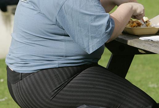 En överviktig man äter vid ett bord utomhus i London. Foto: AP Photo/Kirsty Wigglesworth