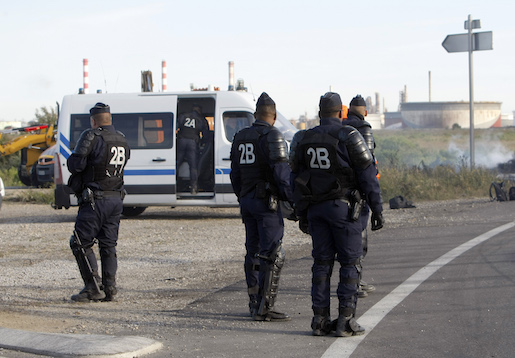 Riot police hold their positions along the road leading to a refinery after they removed barricades set up by striking workers in Fos sur Mer, southern France,Tuesday, May 24, 2016. French police have dislodged protesters blocking a key fuel depot on the Mediterranean, as gasoline shortages spread around the country amid increasingly tense labor actions. (AP Photo/Claude Paris)