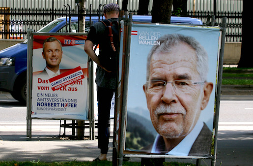 A man walks between election posters of Alexander Van der Bellen, candidate for presidential elections and former head of the Austrian Greens, right, and Norbert Hofer, candidate for presidential elections of Austria's right-wing Freedom Party, FPOE, left, in Vienna, Austria, Monday, May 23, 2016. The Eurosceptic, anti-immigration right-winger Norbert Hofer, and his left-leaning rival are neck and neck in Austria's presidential election a day after polls closed, and officials are now counting absentee ballots to determine who will win. (AP Photo/Ronald Zak)