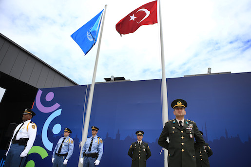 United Nations security personnel, left and Turkish armed forces officers, right, attend a flag raising ceremony, marking the opening of business at the World Humanitarian Summit, in Istanbul, Saturday, May 21, 2016. World leaders and representatives of humanitarian organisations from across the globe converge in Istanbul on May 23-24, 2016 for the first World Humanitarian Summit, focused on how to reform a system many judge broken. (AP Photo/Lefteris Pitarakis)