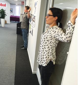 Friskvård kan även vara några minuters stretch på jobbet. Här visar Linda Flood och Anders Emretsson på Arbetets redaktion hur det kan gå till.Foto: Liv Beckström