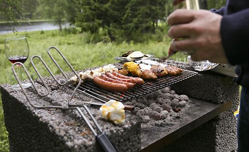 EDSBYN 2013-06-22 En man med en ˆlburk i handen stÂr vid en murad grill och grillar korv, kˆtt och grˆnsaker vid ‰lven Voxnan i H‰lsingland. Foto: Helena Landstedt / SCANPIX / kod 76091