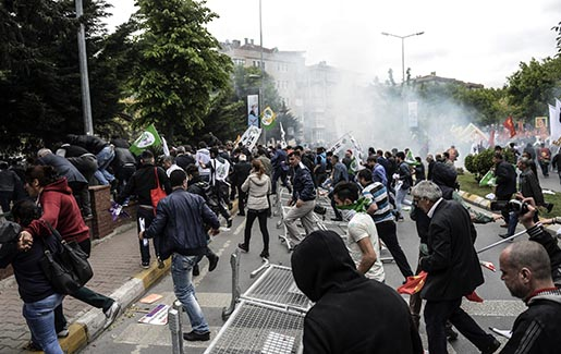 People run as riot police use tear gas to disperse crowds during May Day demonstrations, in Istanbul, Sunday, May 1, 2016. Security forces prevented leftist groups trying to reach city's iconic Taksim Square to celebrate May Day. Turkish police used tear gas and water cannons Sunday to disperse dozens of May Day demonstrators in Istanbul. Small scuffles broke out between police and demonstrators trying to reach Istanbul's iconic Taksim Square. Taksim has symbolic meaning as the center of protests in which 34 people were killed in 1977. (AP Photo)
