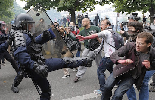 Riot police officers clash with protestors during a demonstration held as part of nationwide labor actions in Paris, France, Thursday, May 26, 2016. French protesters scuffled with police, dock workers set off smoke bombs and union activists disrupted fuel supplies and nuclear plants Thursday in the biggest challenge yet to President Francois Hollande's government as it tries to give employers more flexibility (AP Photo/Francois Mori)