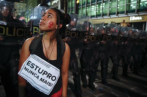 """""""Aldrig mer våldtäkt"""", står det på skylten som denna demonstrant har runt halsen. Foto: AP /Andre Penner"""