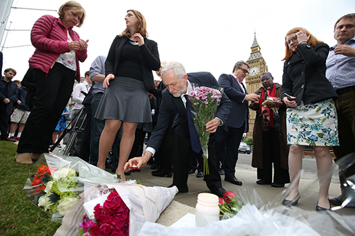 Labour Party leader Jeremy Corbyn, centre, lays a candle as he and deputy leader Tom Watson, centre rear, Thursday June 16, 2016, attend an impromptu vigil at Parliament Square opposite the Palace of Westminster, central London, following the death of Labour Member of Parliament, Jo Cox. The British lawmaker who campaigned for the country to stay in the European Union was killed Thursday by a gun- and knife-wielding attacker in her small-town constituency, a tragedy that brought the country's fierce, divisive referendum campaign to a shocked standstill. (Philip Toscano/PA via AP) UNITED KINGDOM OUT NO SALES NO ARCHIVE