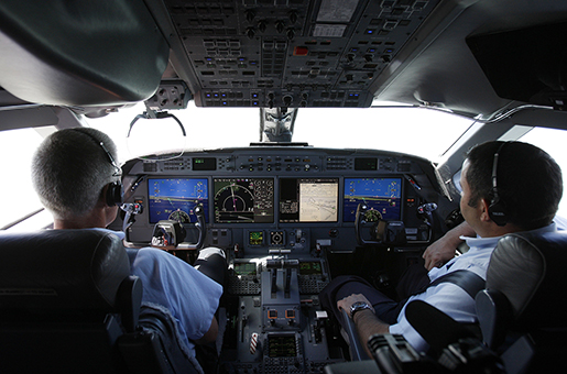 "In this photo taken Sunday July 18, 2010 co-pilot, Paul Mrocka, left, and senior pilot John Tutun look at the Honeywell Aerospace synthetic vison display, left and right, in the cockpit of a Gulfstream jet during a test flight to demonstrate the safety technology on the eve of Farnborough International Airshow, Farnborough, England. Flying over the white cliffs of Dover, the eyes of the two pilots of the Gulfstream 450 jet are glued to a flight deck display, rather than gazing out at southern England's rare almost cloudless sky, as they head toward a nearby runway. Honeywell pilot John Tuten and his co-pilot are testing out what the U.S. aviation company calls the ""cockpit of the future"" _ technology designed as much to meet ever increasing demands for fuel efficiency as to improve aviation safety. (AP Photo/Sang Tan)"