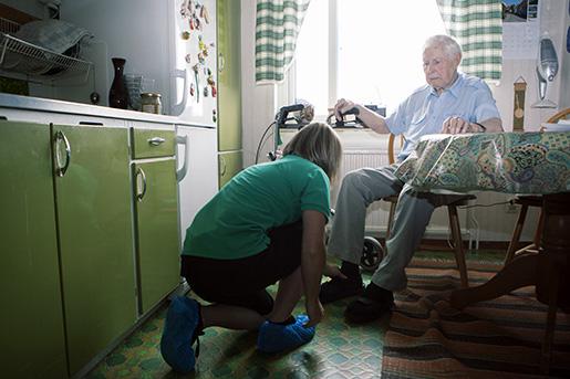 Kamilla Sjödin besöker Arne Nordin och hjälper honom med skorna inför besök hos vårdcentralen.Foto: Mats Andersson / TT