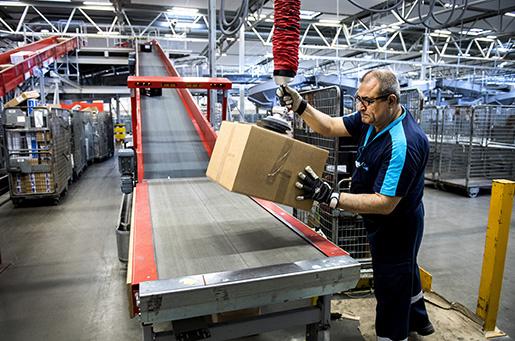 Ibrahim Malgir använder en vacuumslang för att lyfta paketen. De kan väga upp till 35 kilo. E-handeln har dessutom ökat flödet av paket. Foto: Marcus Ericsson/TT