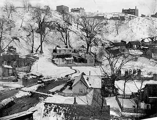 """Från 1880-talet var dalgången utanför St Paul i Minnesota känd som Swede Hollow, ett av stadens värsta slumområden. Här bodde minst tusen människor, de flesta svenskar, i fallfärdiga skjul. Ett tidningsreportage från tiden berättar om små linhåriga barn i illasittande smutsiga kläder som """"tjattrar med varandra på ett obegripligt språk"""". Genom dalen rinner den svårt nedsmutsade Phalen Creek.Foto: Wikimedia"""