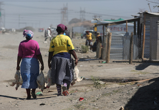 In this Aug. 12, 2016 photo, women with chickens walk along a dirt paths to their homes among hundreds of shacks which house mineworkers, in Marikana South Africa. Four years after South African police shot dead 34 miners driven to fury by poor living conditions, the British mining company Lonmin has failed to provide the homes it promised for several thousand workers, Amnesty International says. (AP Photo/Denis Farrell)