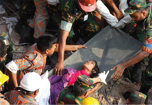En överlevare dras fram ur ruinerna efter den kollapsade fabriksbyggnaden Rana Plaza i Dhaka. I Modeslavar möter författarna flera som överlevde katastrofen, där 1 100 människor miste livet.Foto: A. M. Ahad