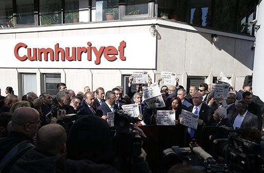 """Journalists and lawmakers hold copies of the latest Cumhuriyet newspaper outside its Istanbul headquarters after police detained chief editor Murat Sabuncu and two columnists of Turkey's opposition Cumhuriyet and had warrants to detain 10 other senior staff members, in Istanbul, Monday, Oct. 31, 2016, the state-run-Anadolu Agency reported, amid growing fears over Turkey's widening crackdown on dissenting voices. Cumhuriyet's headline reads: """"The coup against opposition again."""" (AP Photo/Emrah Gurel)"""