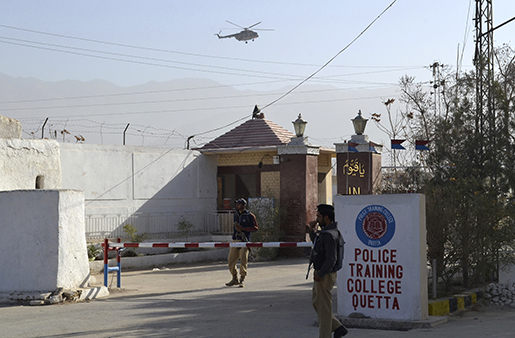 Pakistani police officers stand guard outside a police training center which was attacked by militants in Quetta, Pakistan, Tuesday, Oct. 25, 2016. Gunmen stormed a police training center late Monday in Pakistan's restive Baluchistan province and detonated explosive vests, killing dozens of police trainees and wounding many others, authorities said. (AP Photo/Arshad Butt)