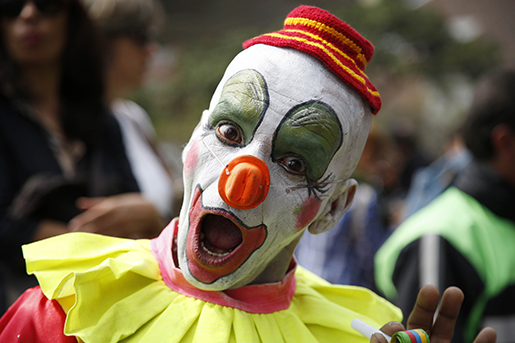 A clown performs in the inaugural parade marking the 15th Iberoamerican Festival of Theater, FITB, in Bogota, Colombia, Saturday, March 12, 2016. The festival celebrates the performing arts, including circus, cabaret, musicals, live bands, dance, and theater. (AP Photo/Fernando Vergara)