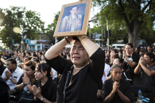 A Thai woman cries as she holds a picture of the late King Bhumibol Adulyadej as others clasp their hands to pay their last respect to a passing van carrying the body of their king outside Grand Palace in Bangkok, Thailand Friday, Oct. 14, 2016. Bhumibol, the world's longest reigning monarch, died on Thursday at the age of 88. (AP Photo/Wason Wanichakorn)