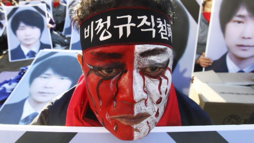 "A worker with his face painted, stands in front of portraits of Choi Jong-beom as he participates in a rally against government's labor policy in front of the Seoul City Hall in Seoul, South Korea, Sunday, Nov. 10, 2013. About 20,000 members of the Korean Confederation of Trade Union demanded better working condition and the end to companies' use of temporary employees. Choi Jong-beom was a Samsung Electronics Service employee, who reportedly killed himself after leaving a message complaining about harsh working conditions. The headband reads ""Abolition of temporary employees."" (AP Photo/Ahn Young-joon)"