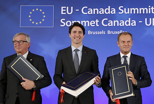 Canadian Prime Minister Justin Trudeau, center, stands with European Commission President Jean-Claude Juncker, left, and European Council President Donald Tusk after signing the Comprehensive Economic and Trade Agreement (CETA) during an EU-Canada summit at the European Council building in Brussels, Sunday, Oct. 30, 2016.(Francois Lenoir/Pool Photo via AP)