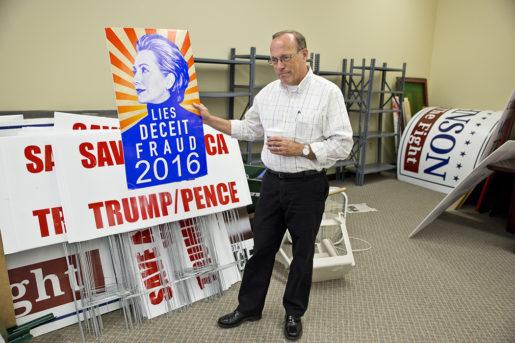 Mark Munroe på Republikanernas kontor håller upp en av affischerna som kallar Clinton för bedragare.