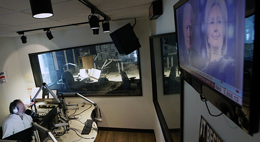 Images of Republican and Democratic presidential candidates Donald Trump and Hillary Clinton are displayed on a television screen in the studio of radio talk show host Rick Roberts during his program in Dallas on Tuesday, Sept. 6, 2016. The station estimates Roberts' audience is about two-thirds male and overwhelmingly white, though women and minorities also call in on this day and you needn't look far, even in Roberts' own studio, to find a white man who doesn't subscribe to conservative orthodoxy. (AP Photo/LM Otero)