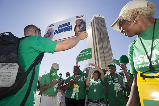 Brian Poncin, of Chicago, a member of the American Federation of State, County and Municipal Employees (AFSCME) union, Local 2858, holds a sign with images of Republican presidential nominee Donald Trump and running mate Indiana Gov. Mike Pence during a rally at the Trump International Hotel Las Vegas in Las Vegas, Wednesday, July 20, 2016. AFSCME members, in Las Vegas for a convention, came out in support of the Culinary Workers Union, Local 226, which is trying to unionize workers at the hotel. (Steve Marcus/Las Vegas Sun via AP)
