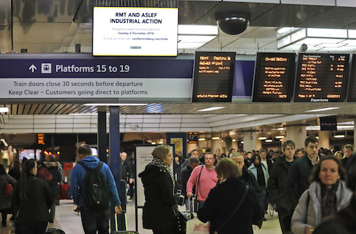 Travelers pass a sign which refers to the strike action of Southern railway conductors at Victoria Station in London, Monday, Dec. 19, 2016. Southern and Gatwick RMT conductor's are on strike on Monday and Tuesday. (AP Photo/Frank Augstein)