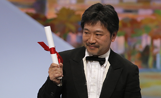 Director Kore-eda Hirokazu holds up the Jury's Prize award for his film Like Father, Like Son which was presented by actress Rossy de Palma during an awards ceremony at the 66th international film festival, in Cannes, southern France, Sunday, May 26, 2013. (AP Photo/Francois Mori)