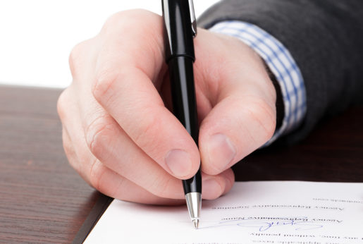 Male signing documents with black pen on a desk
