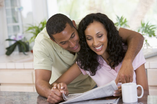 Couple in kitchen with newspaper and coffee smiling