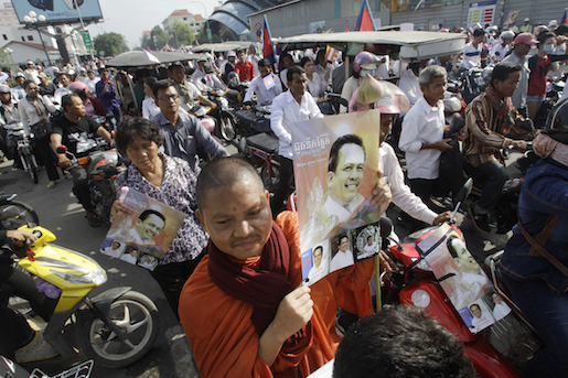 A Cambodian Buddhist monk, foreground, holds a portrait of Cambodia prominent political analyst Kem Ley as he takes part in a funeral procession of Kem Ley in Phnom Penh, Cambodia, Sunday, July 24, 2016. Tens of thousands of Cambodians marched Sunday, in the funeral procession for the leading government critic who was fatally shot in an attack that raised suspicion of a political conspiracy. (AP Photo/Heng Sinith)