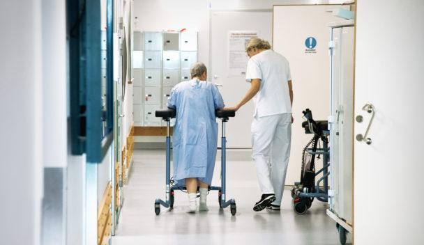 en sköterska och en patient går i sjukkorridor