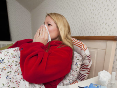 Kvinna förkyld i sängen
